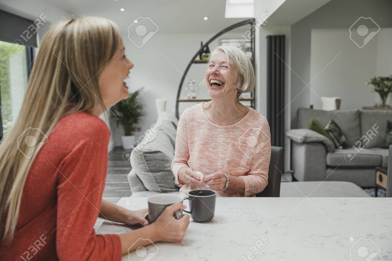 Senior woman is enjoying a catch up with her daughter. They are sitting in the kitchen drinking cups of tea. - 84956718