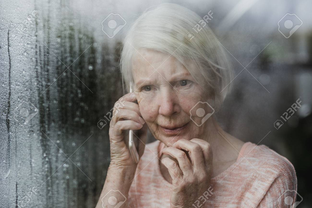 Senior woman is looking worriedly out of the window of her home while talking to someone on the phone. - 85444214