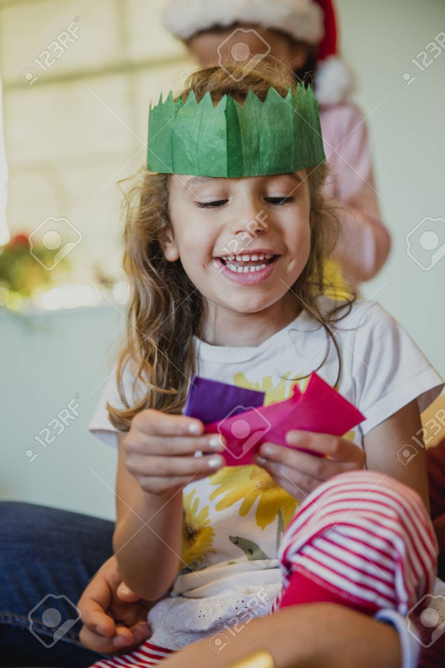 Christmas Crackers Hat.Happy Little Girl Is Playing With All The Hats From The Christmas