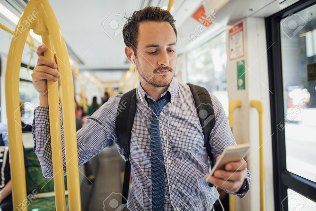 Millennial businessman is commuting on a tram in Melbourne, Victoria. He is watching something on his smart phone with headphones while standing and holding on to the rail. - 100485560