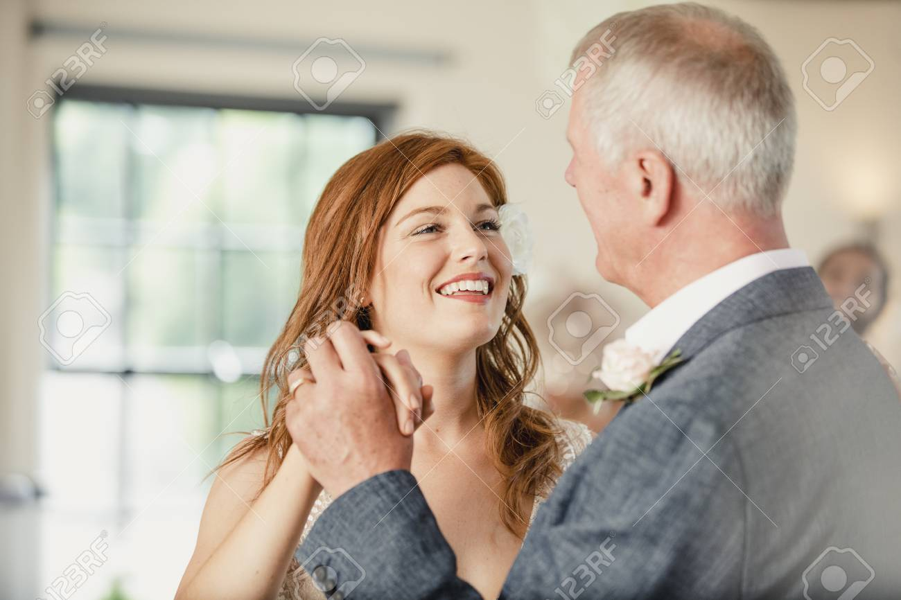 Beautiful bride is enjoying a dance with her father on her wedding day. - 94034909