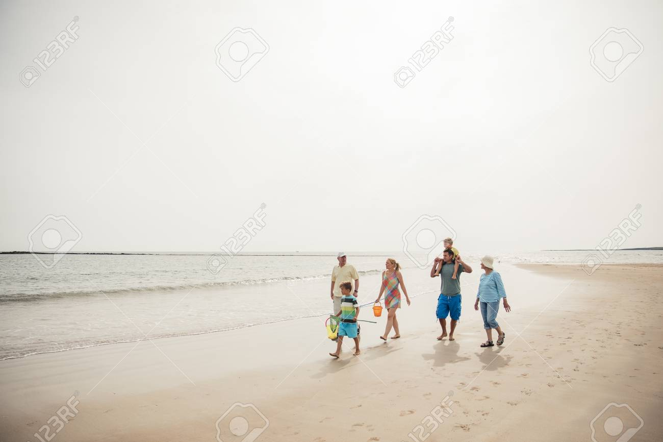 Wide angle view of a family walking along the beach. - 97863089