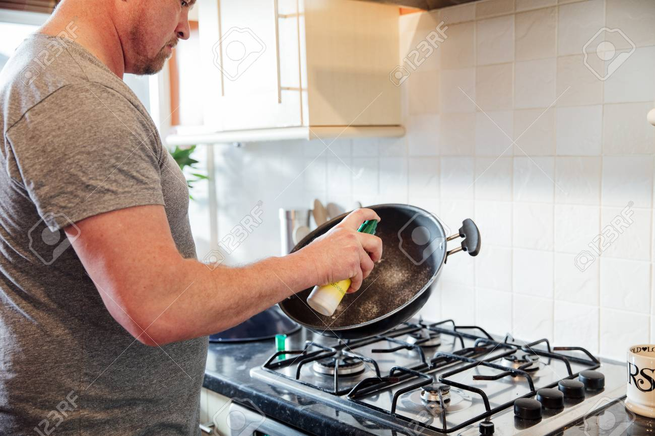 Close up shot of a mature man spraying some frying oil onto a cooking wok in the kitchen of his home. - 100479568