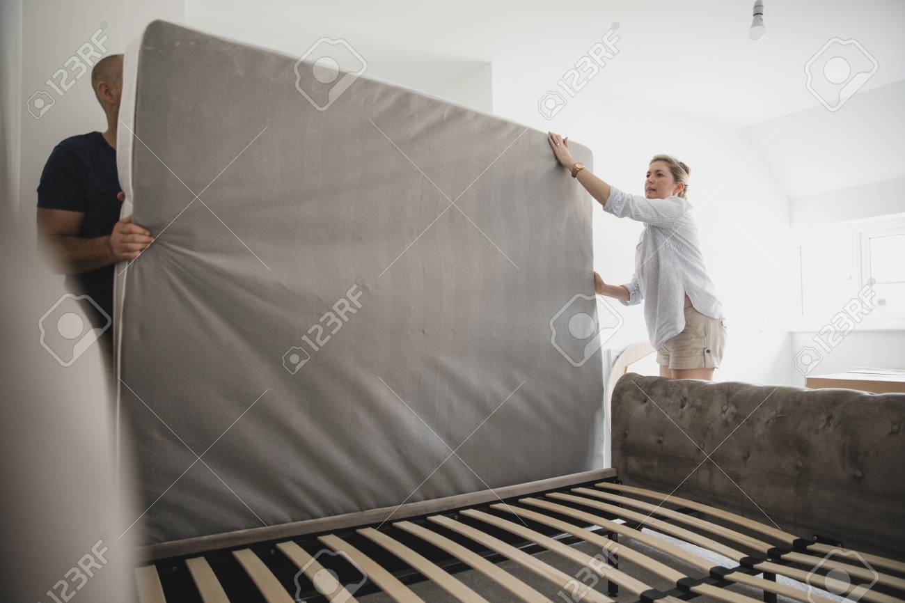 Mature couple are setting up their bed in their new home. - 108206620