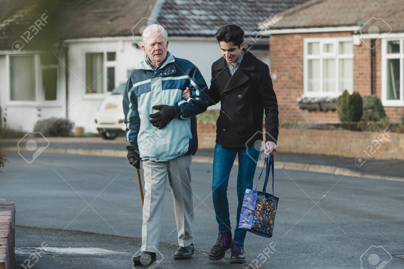 3a107f3b4 Stock Photo - Teenage boy is walking back from the shop with his  grandparent. He is carrying the shopping bag and they are linking arms.
