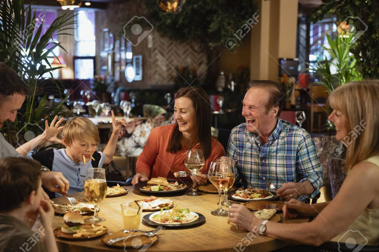 A family having a meal at a restaurant. A young boy is making them all laugh by making a face using food. - 154082030