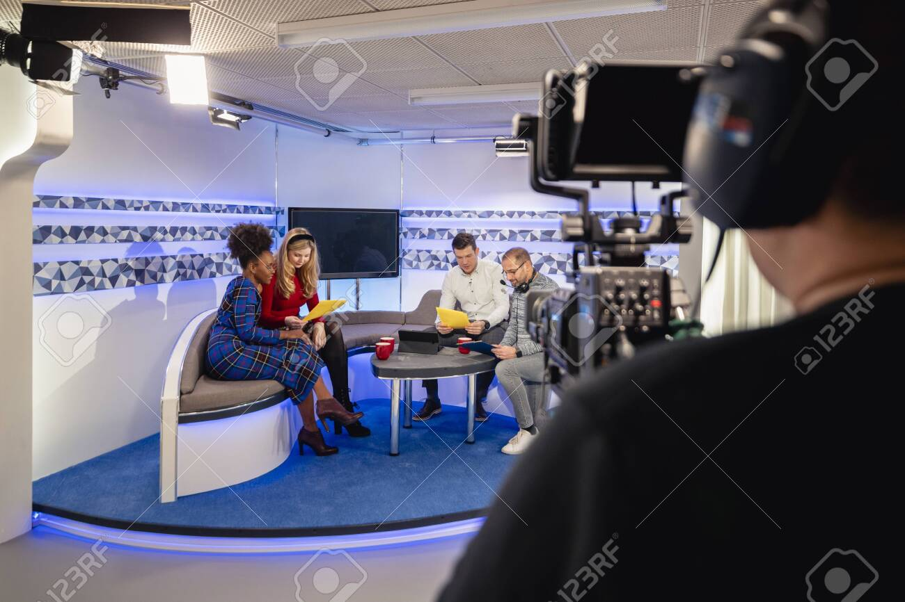 Over the shoulder view of a TV show in the process of being filmed in a studio. The presenters are sitting on the studio sofa while looking at notes and talking to the producer, while the camera man is preparing to start filming again. - 156897455
