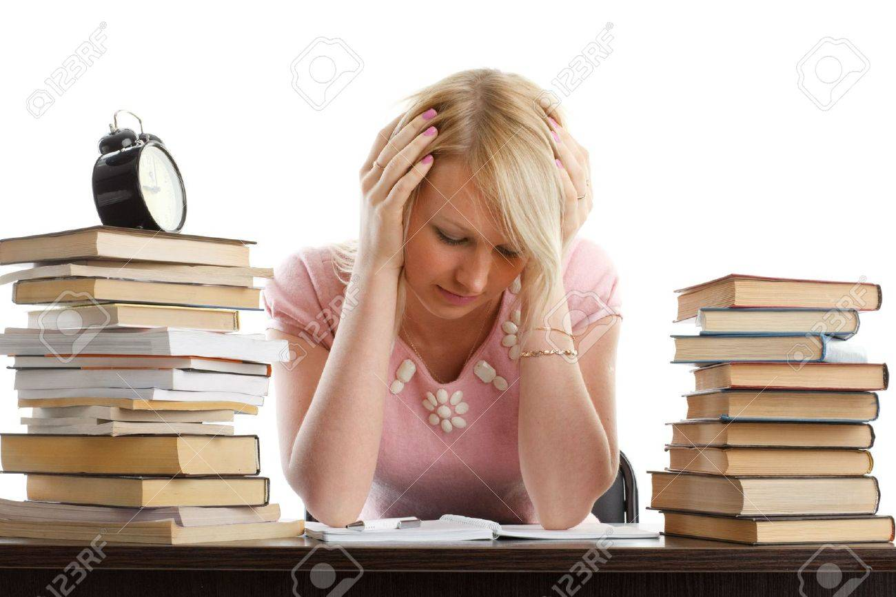 Stressed young woman  at a table among books on a white background Stock Photo - 6506538