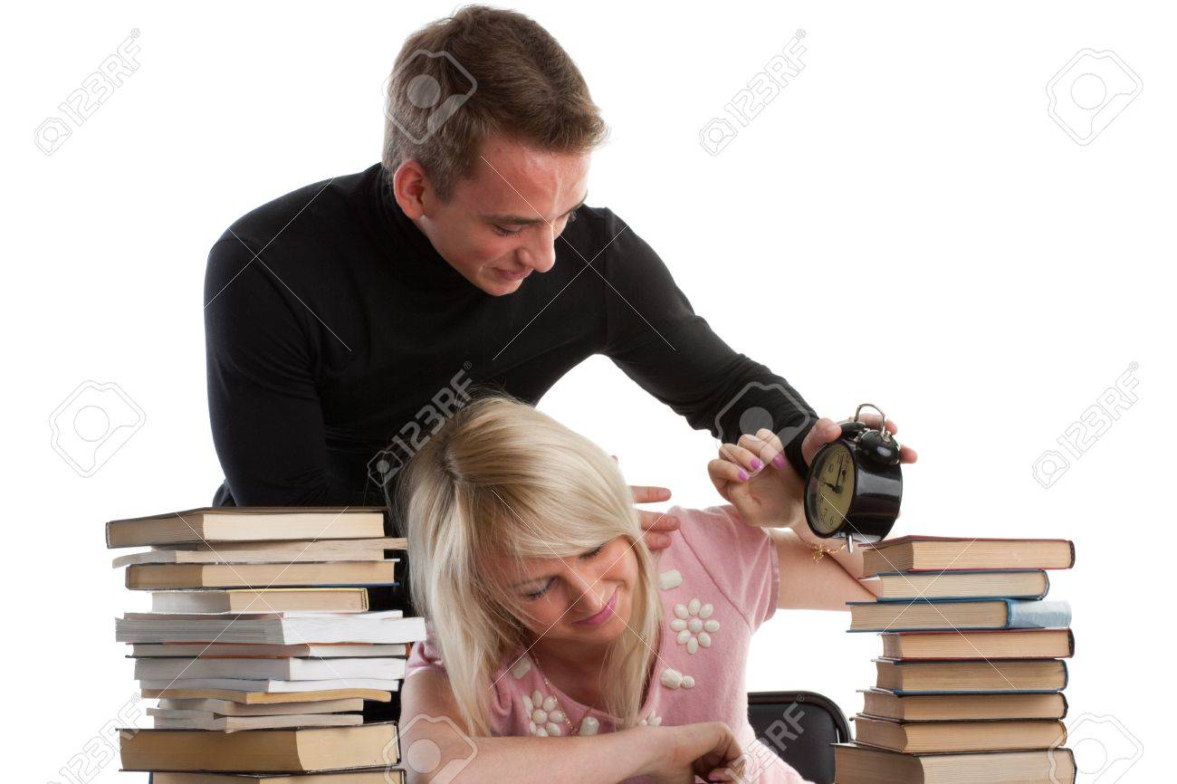 The young man tries to wake the sleeping girl who is late for examination on a white background. Stock Photo - 6878126