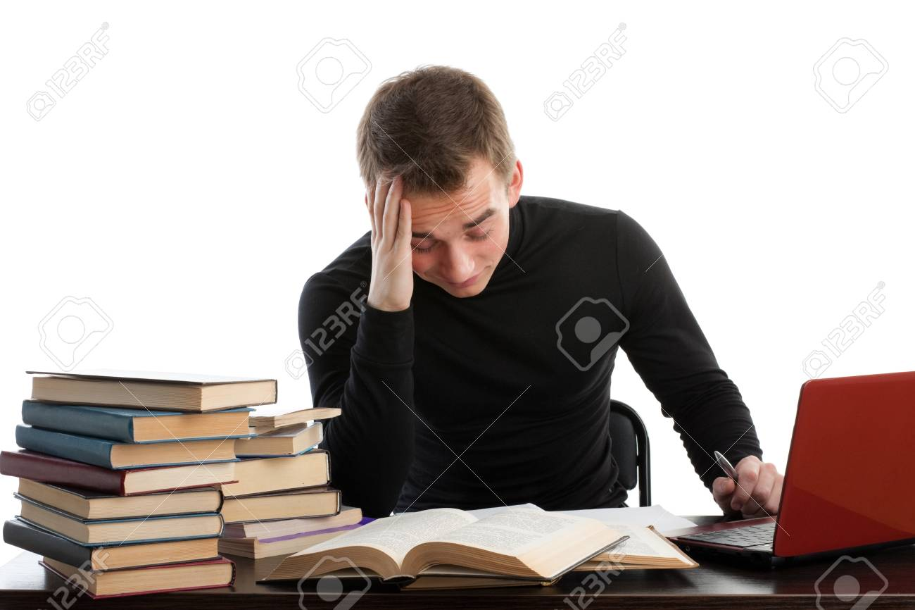 Stressed young man sitting at a table among books and  laptop on a white background Stock Photo - 6878119