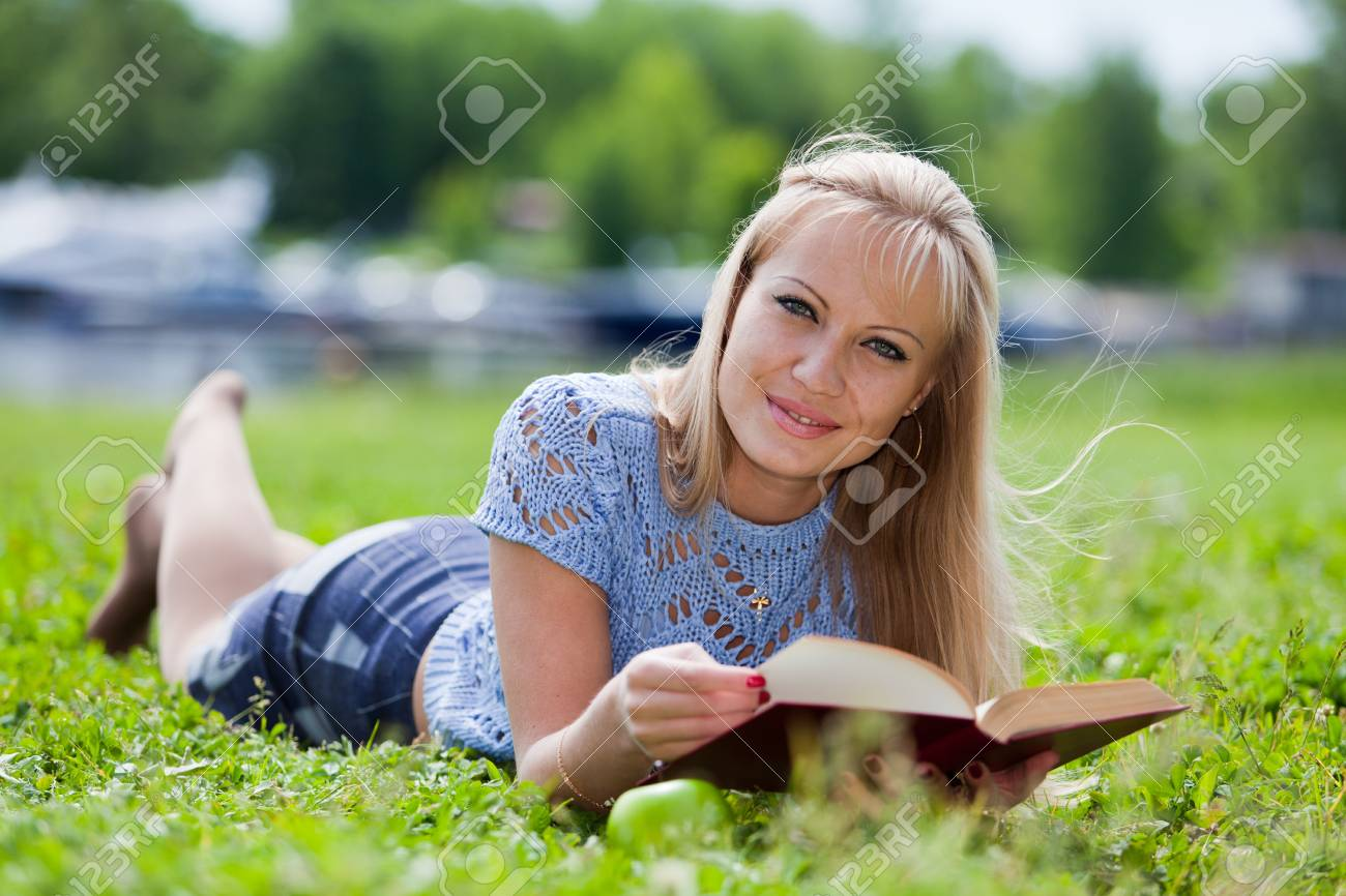 The beautiful young woman  lies on a grass in park with the book and an apple. Stock Photo - 7295368