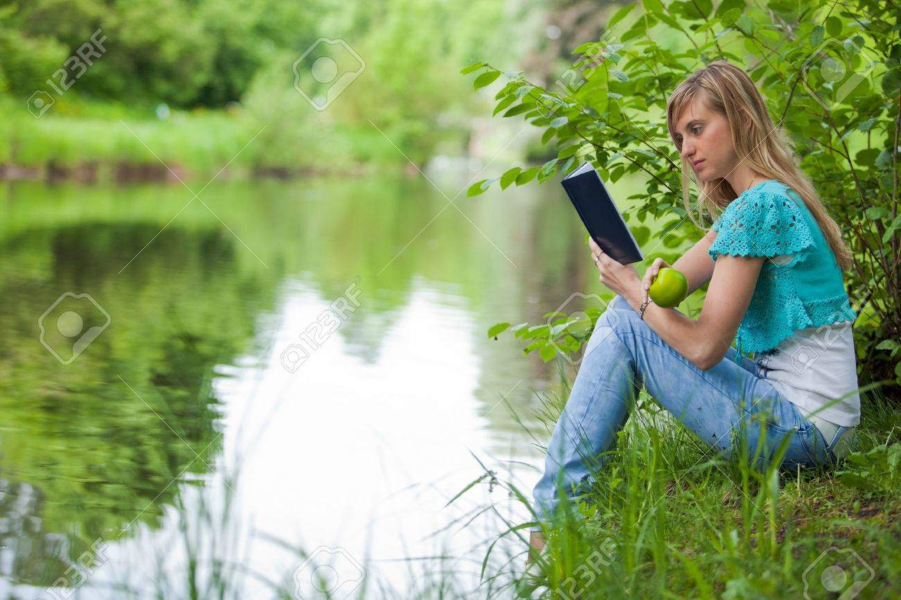 The beautiful young woman sits on a grass in park with the book and an apple. Stock Photo - 7310813