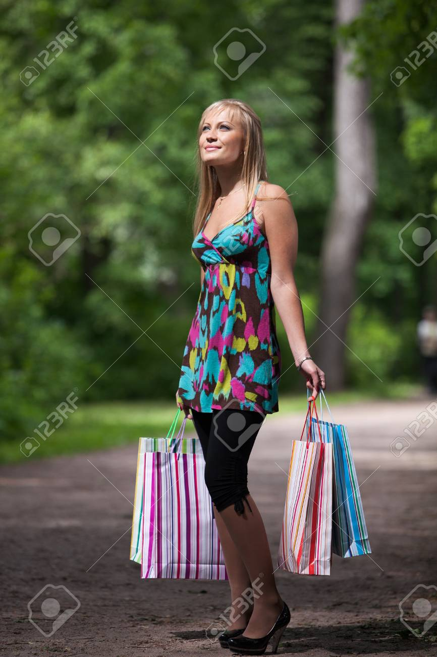 Happy young woman with shopping bags goes home after successful shopping. Outdoors. Stock Photo - 7310821