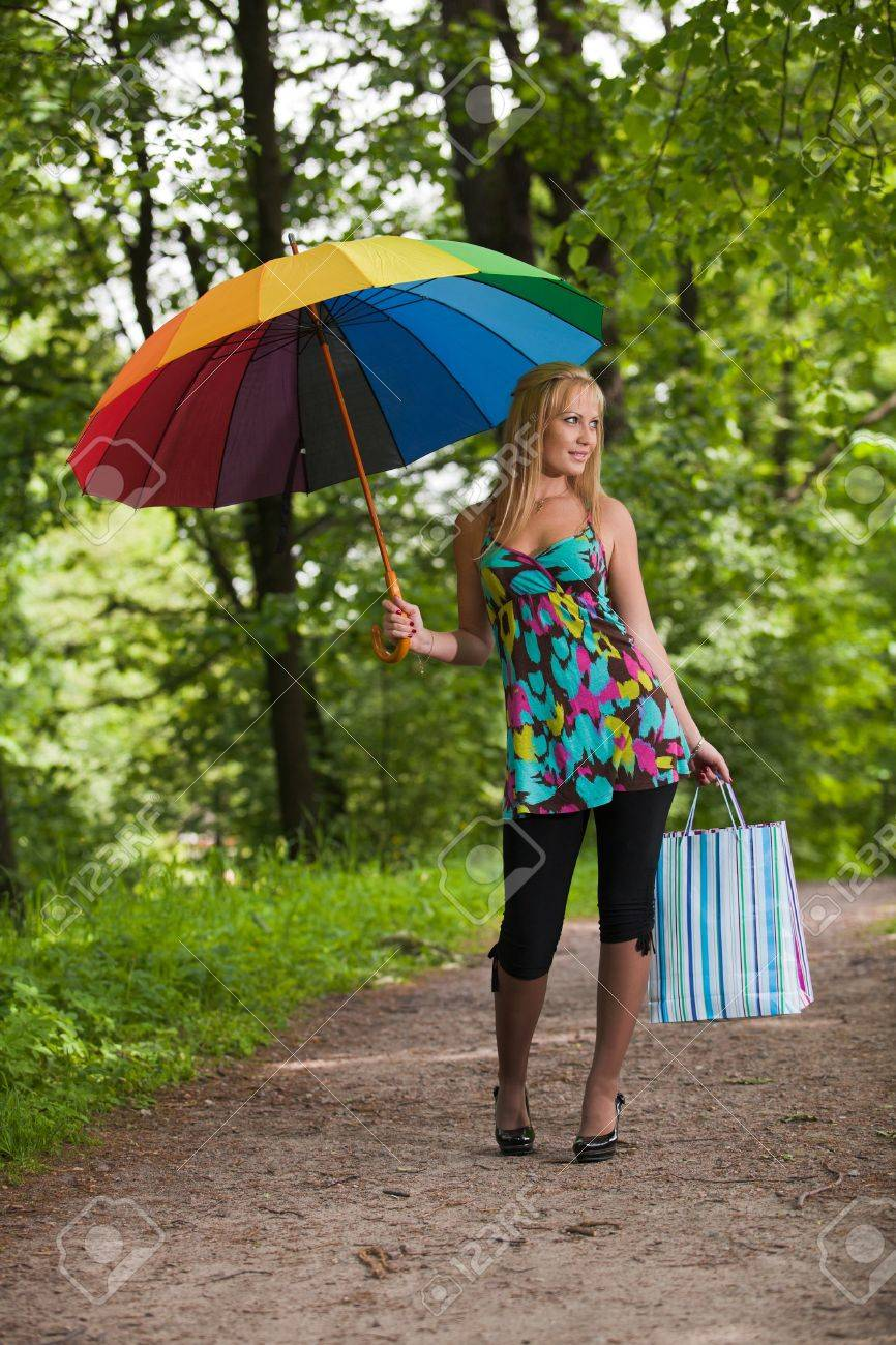 Happy young woman with shopping bags and umbrella goes home after successful shopping. Outdoors. Stock Photo - 7310825