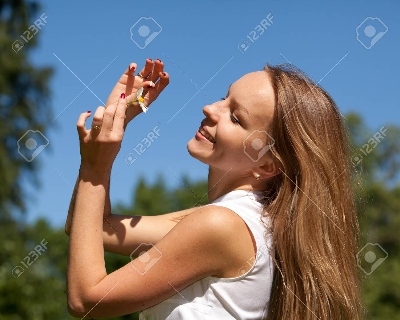 The beautiful young woman with camomile  against of blue sky. Fortune-telling on a camomile. Stock Photo - 7310822