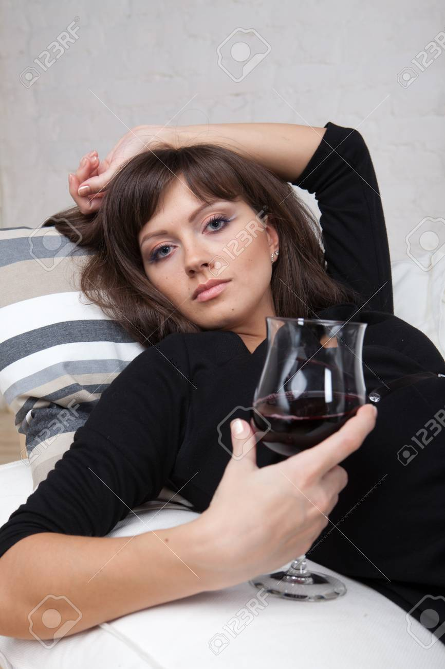 Young woman relaxes at home on the white sofa with a glass of red wine Stock Photo - 7638583