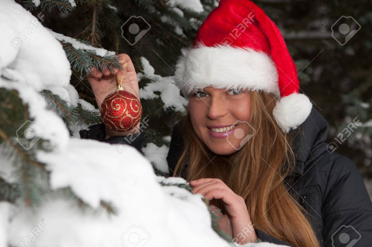 The beautiful girl in a Christmas cap decorates a fur-tree in winter wood. Stock Photo - 8359715