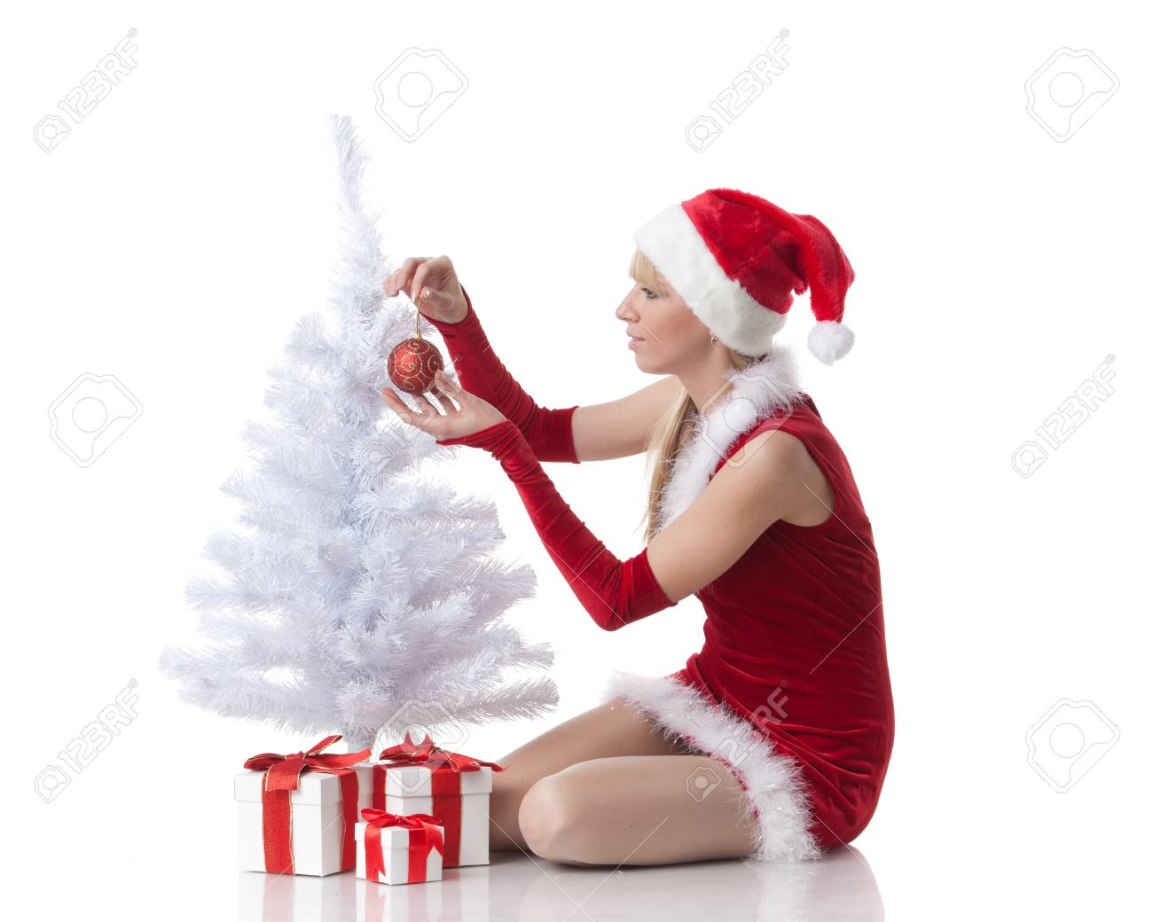 The beautiful girl with a gift in a Santa's cap sits near a Christmas tree on a white background. Stock Photo - 8488964