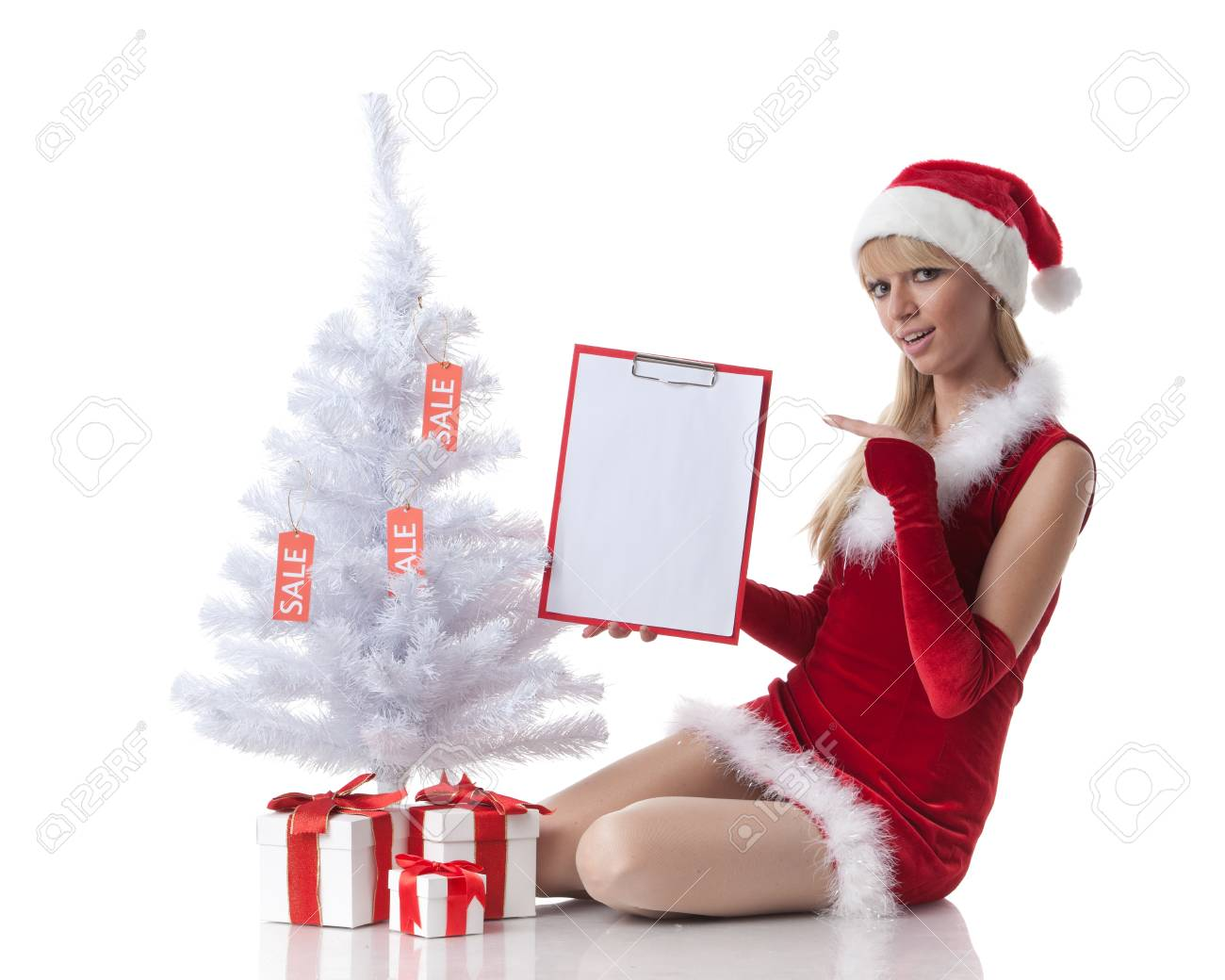The beautiful girl with a gift in a Santa's cap sits near a Christmas tree on a white background. Stock Photo - 8488967