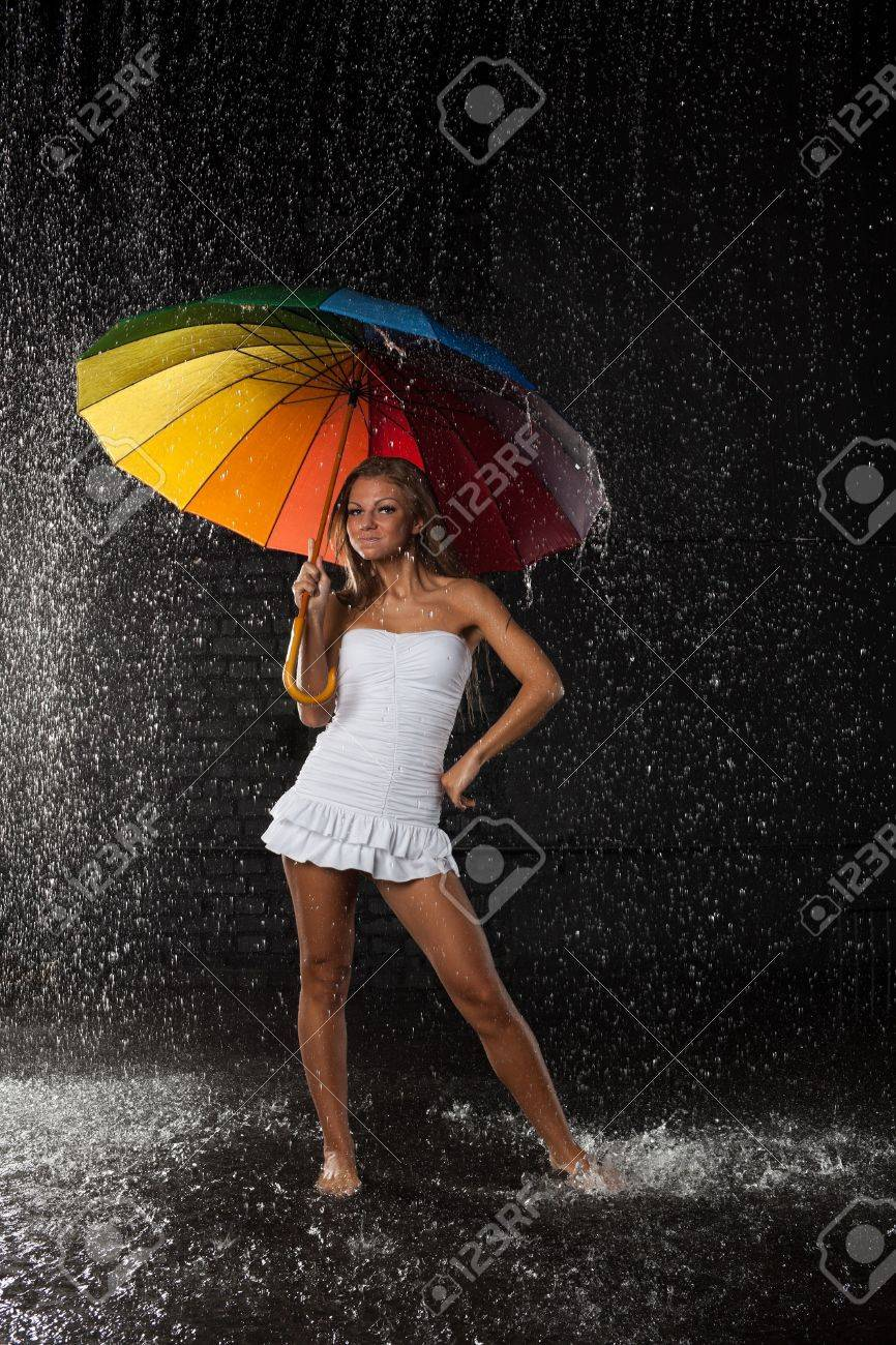 Young pretty woman with multi-coloured umbrella under rain on a black background. Stock Photo - 8806664