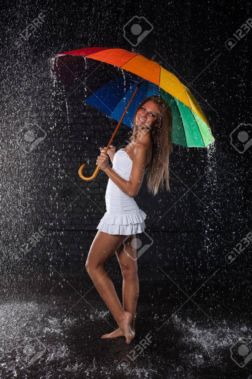 Young pretty woman with multi-coloured umbrella under rain on a black background. Stock Photo - 8923005