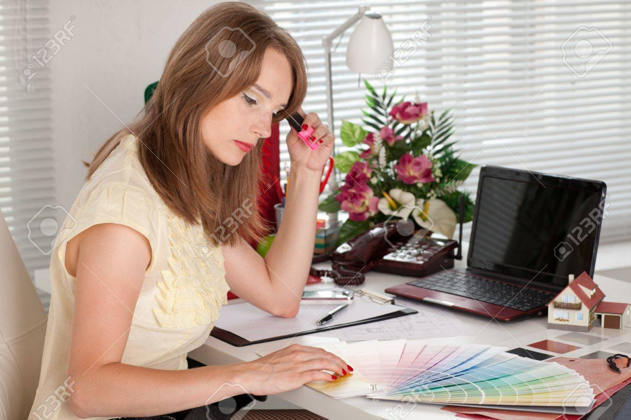 Young female designer of interior sits on the workplace at the office. Stock Photo - 9910130