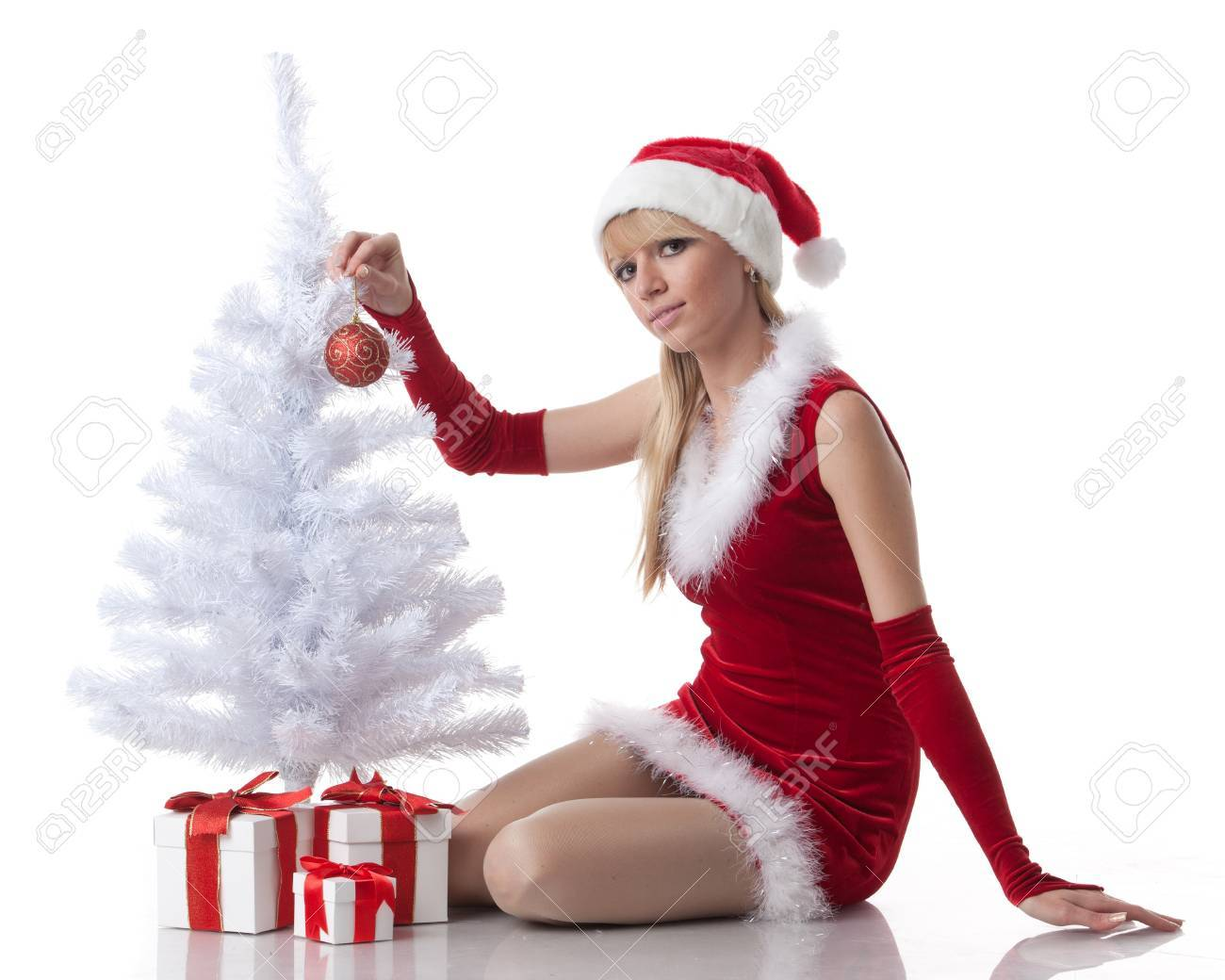 The beautiful girl with a gift in a Santa's cap sits near a Christmas tree on a white background. Stock Photo - 10623601