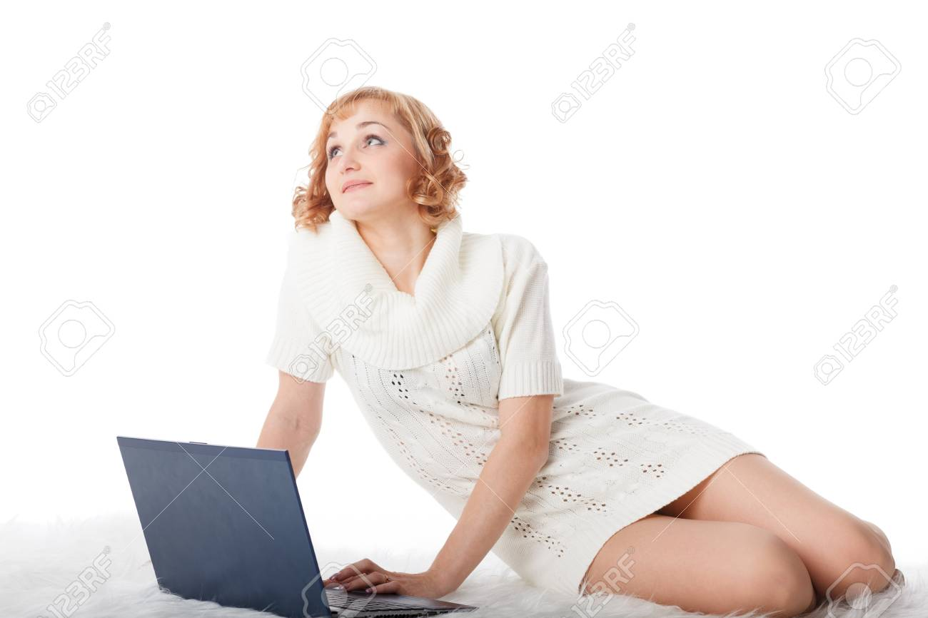 Beautiful young woman with a laptop lies on warm plaid on a white background. Stock Photo - 13670252