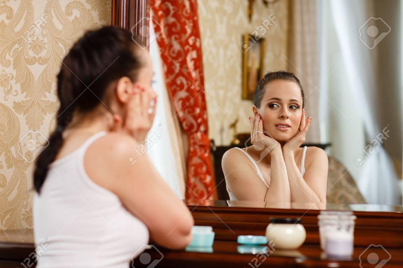 Young woman with cosmetic cream sits before a house  dressing table.Concept body care. Stock Photo - 19356345