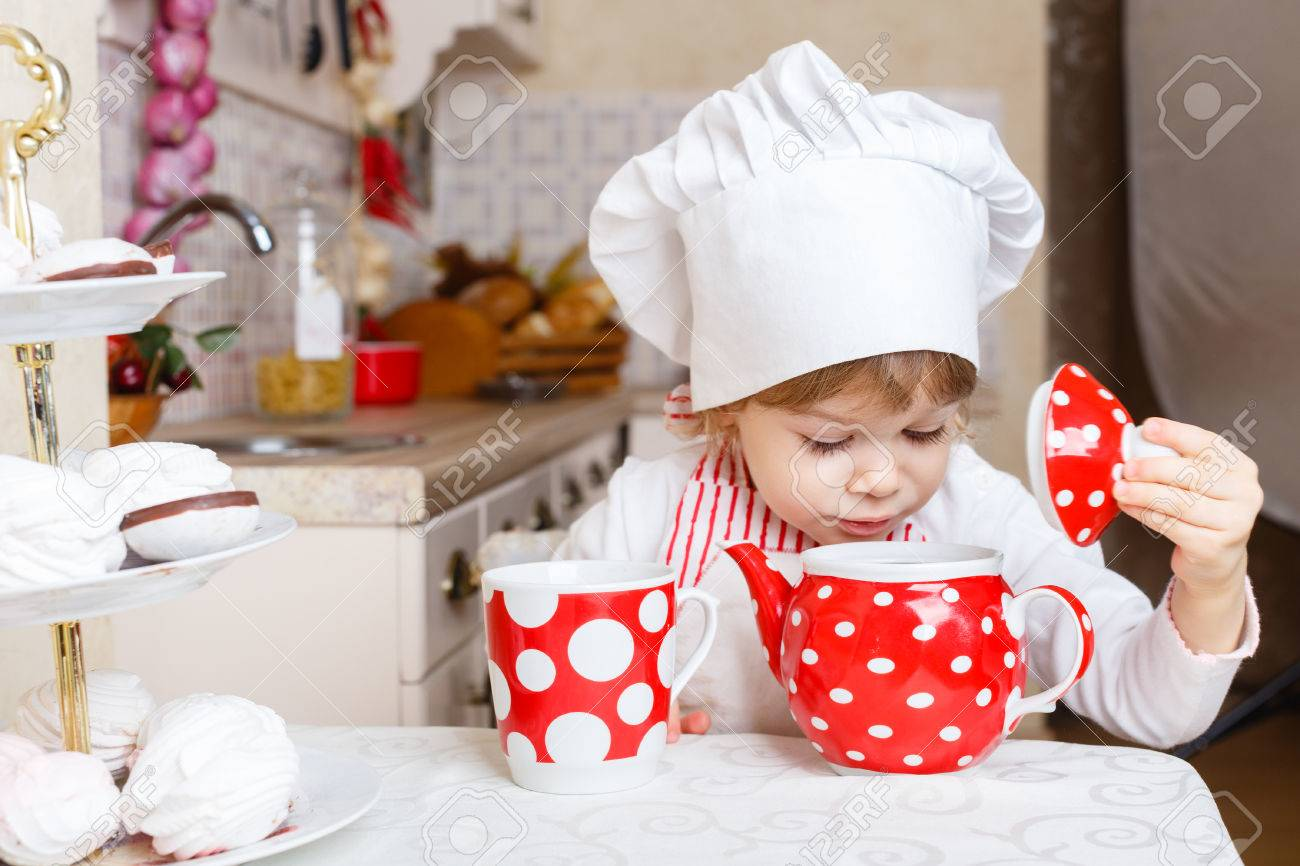 Little girl in apron and cap of the cook with sweet desserts sits at the dining table in the kitchen in the house. Mother's helper. 2 year old. Stock Photo - 27570133