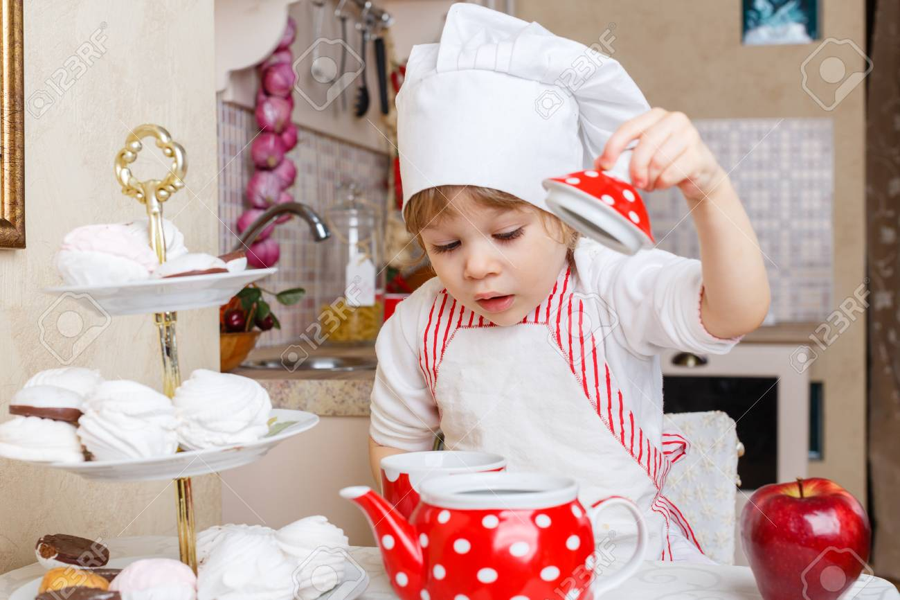 Little girl in apron and cap of the cook with sweet desserts sits at the dining table in the kitchen in the house. Mother's helper. 2 year old. Stock Photo - 27570132