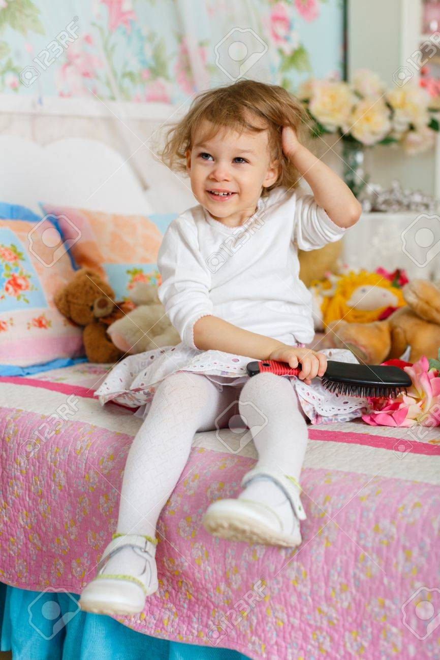 Little girl combing hair sits on the bed in children room. 2 year old. Stock Photo - 27570138