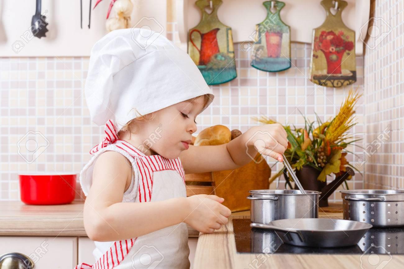Petite Fille En Tablier Et Le Capuchon Du Cuisinier Se Trouve Dans