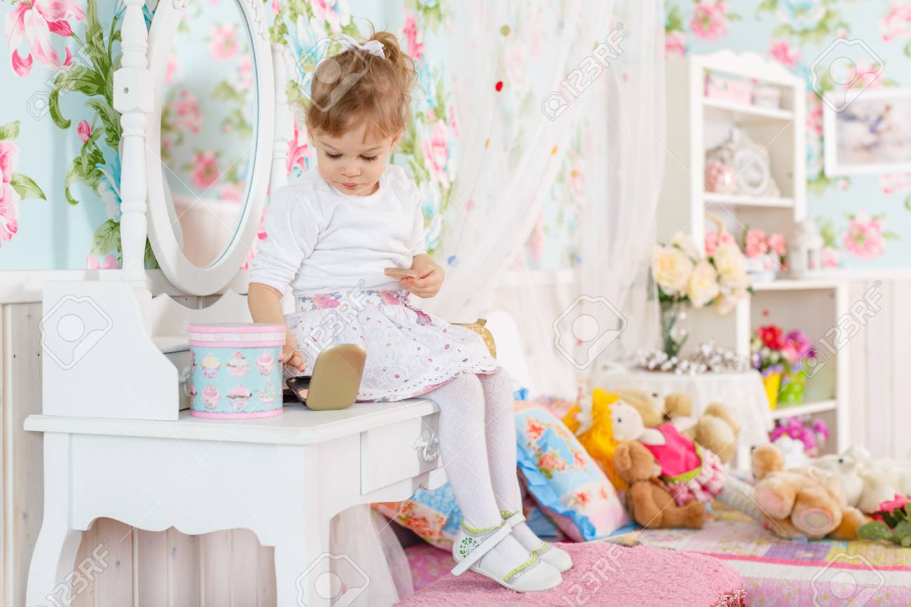 Pretty Little Girl Playing With Cosmetics Near Dressing Table In The Room.  2 Year Old