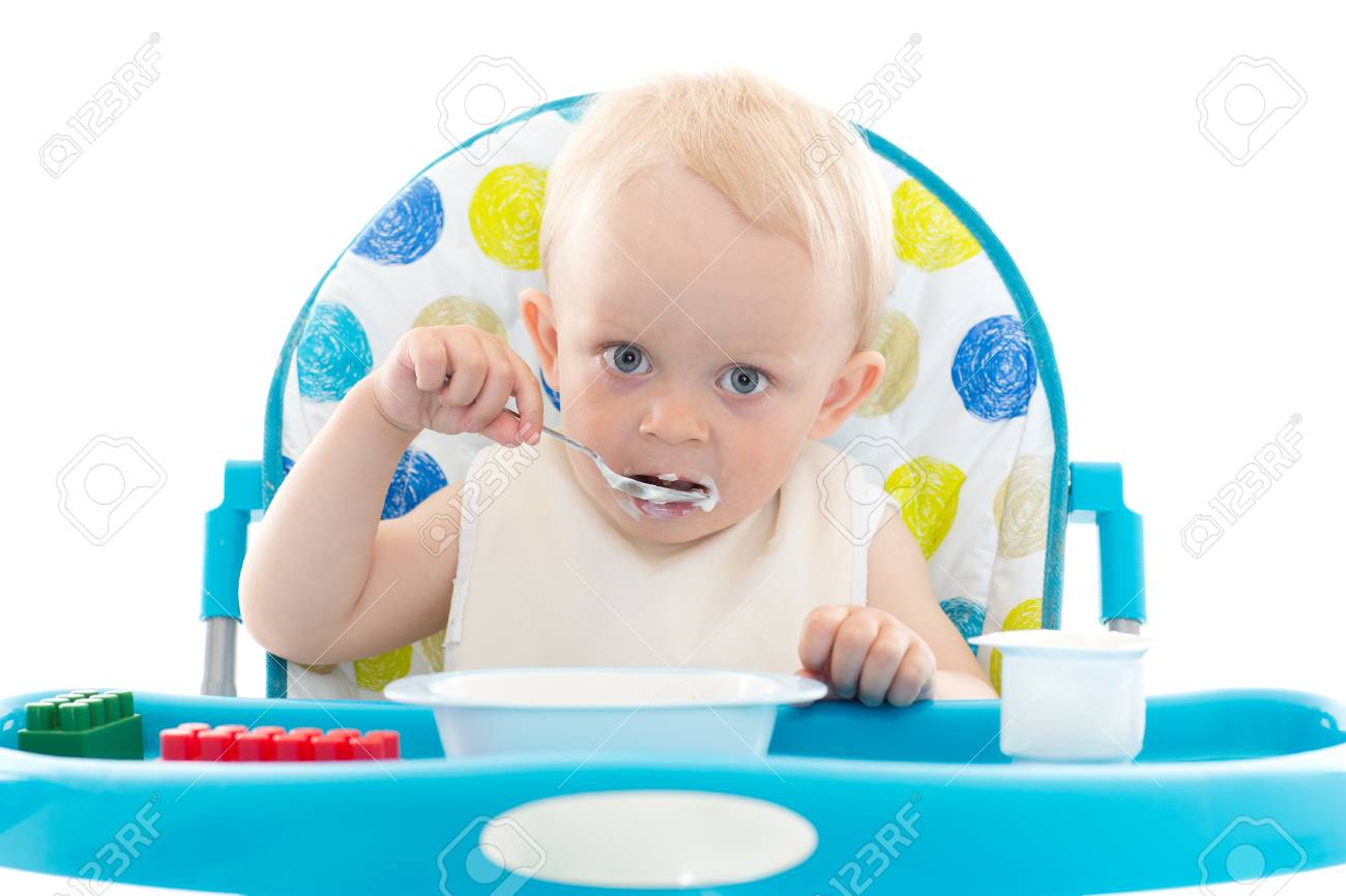 Sweet Baby Learning To Eat With Spoon Sits On Baby Chair On A ...