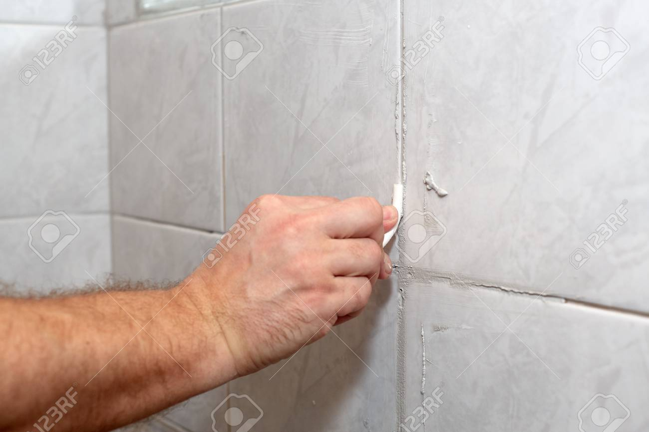 The Male Hand With The Rubber Stick Applies Grout On A Seam Between ...