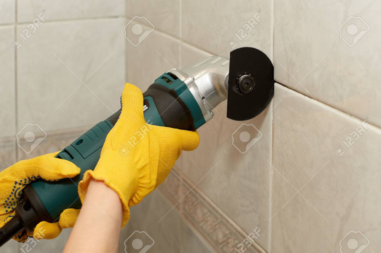 Male hands with renovator multi tool removing the old grout stock male hands with renovator multi tool removing the old grout replacing old grout between dailygadgetfo Images