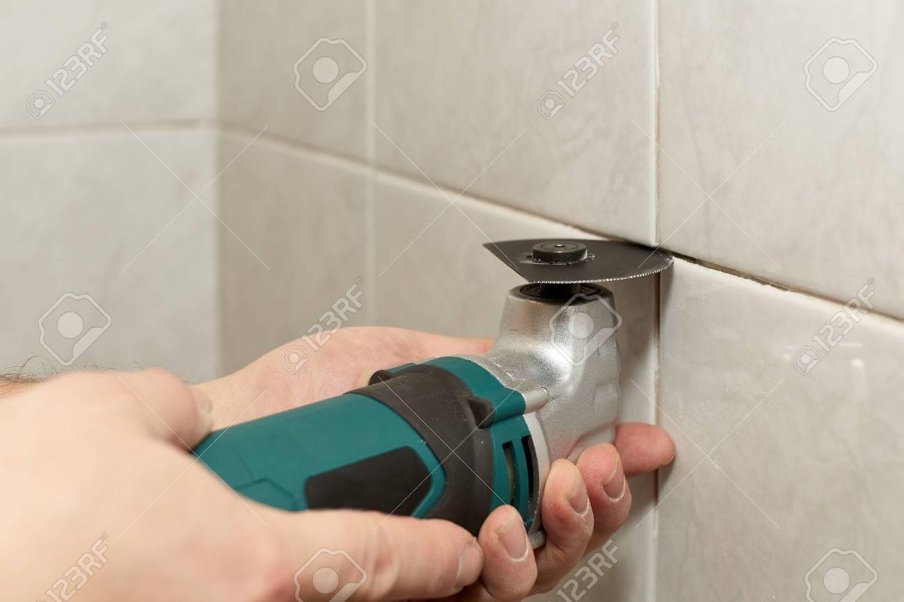 Männliche Hände Mit Renovierer MultiTool Entfernen Der Alten - Fliesen mörtelbett entfernen