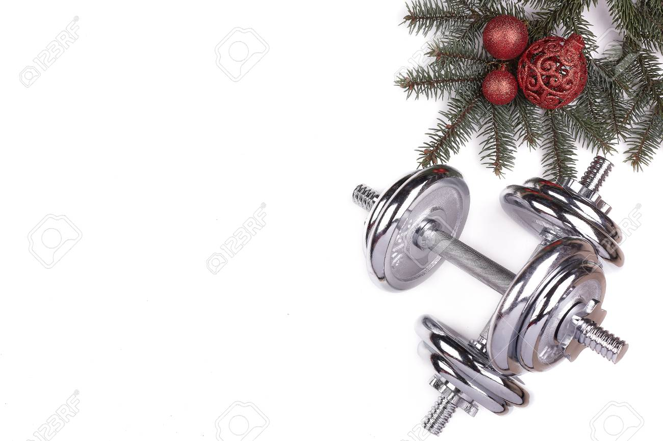 Christmas Sports Background.Dumbbell Fir Tree Branches And Christmas Decorations On A White