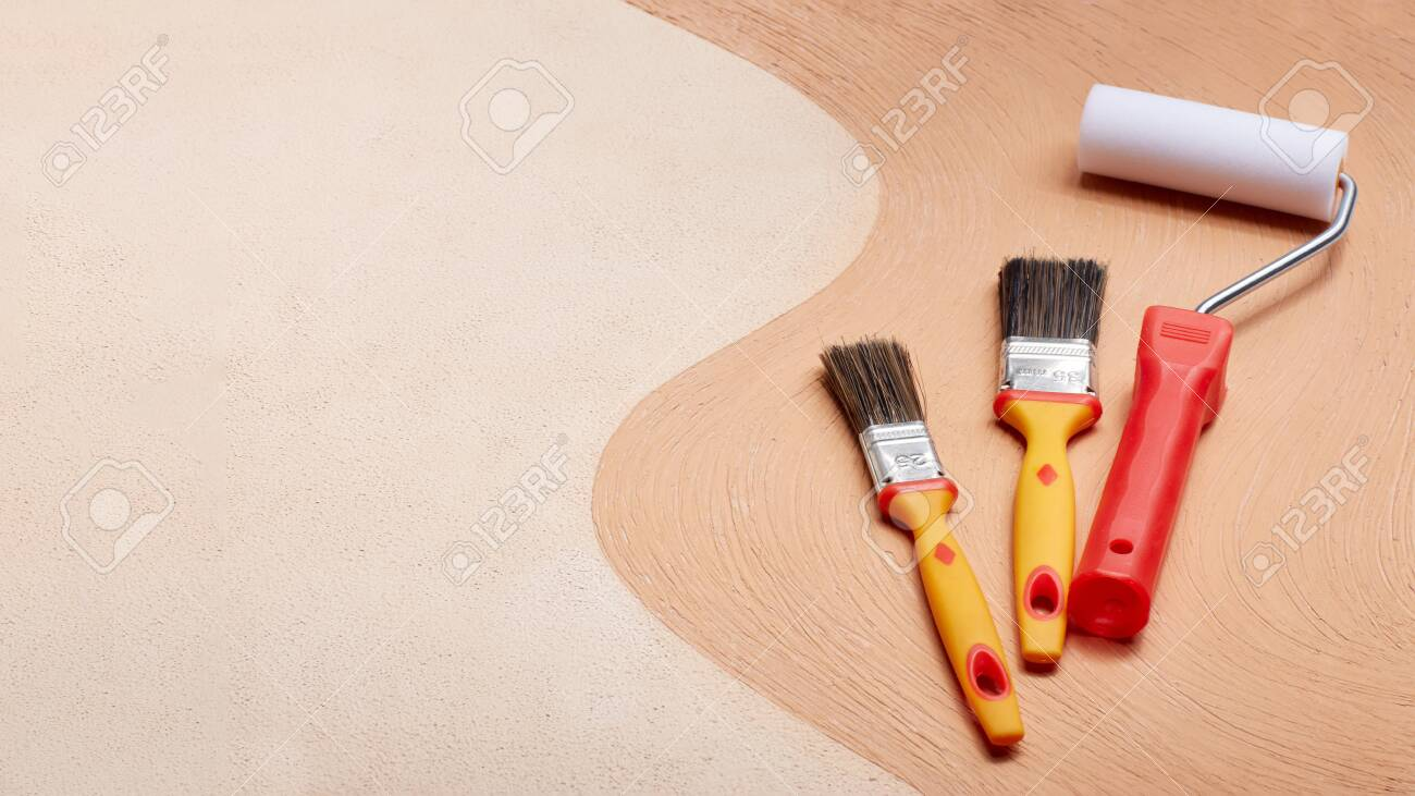 Yellow paint brushes and red roller lying on textural double background consisting of two beige shades. Top view with copy space, Concept of construction or design office - 121914760