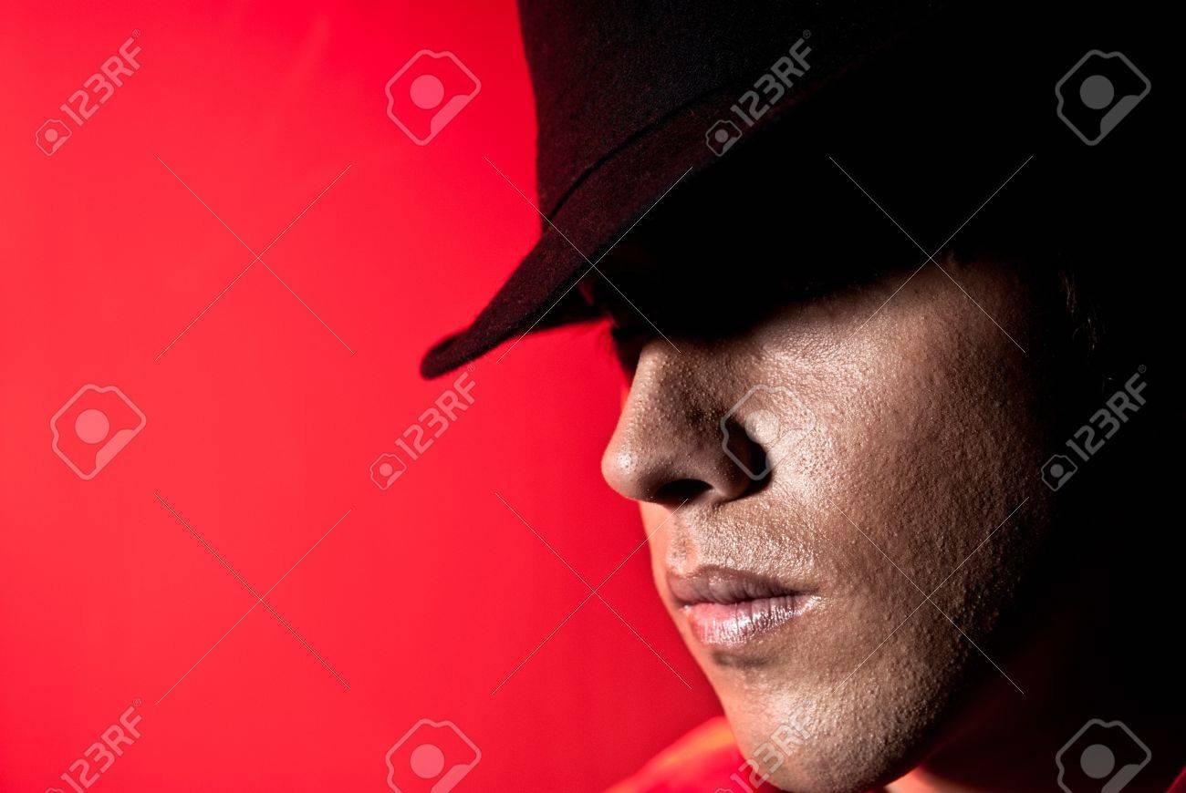 df1ccb7c3fa9a Banque d'images - Portrait bel homme avec un chapeau noir et les yeux  mystère concept de beauté sur fond rouge