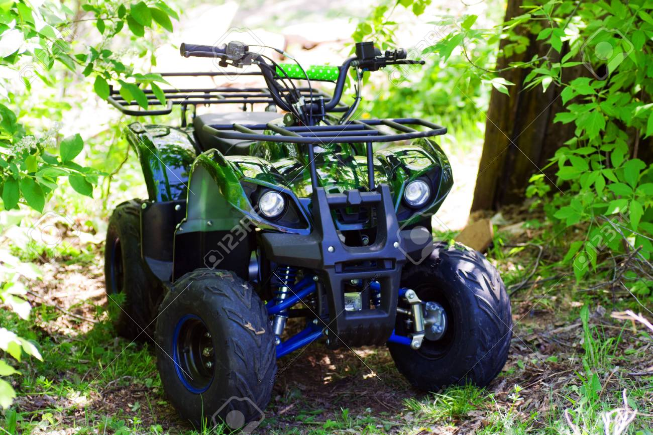 camouflage ATV 125 cc parked in forest