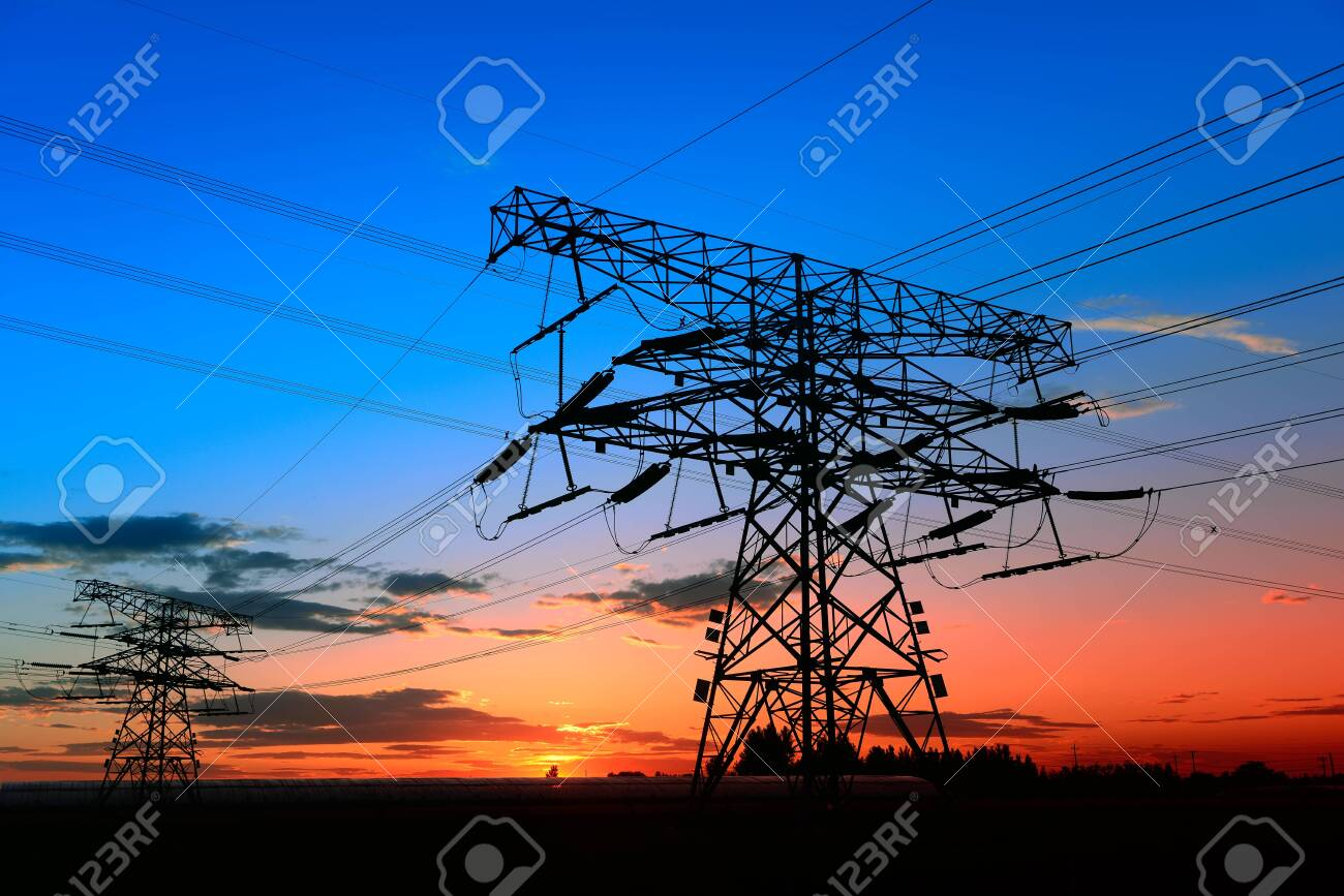 High voltage towers, silhouetted in the setting sun - 143484338