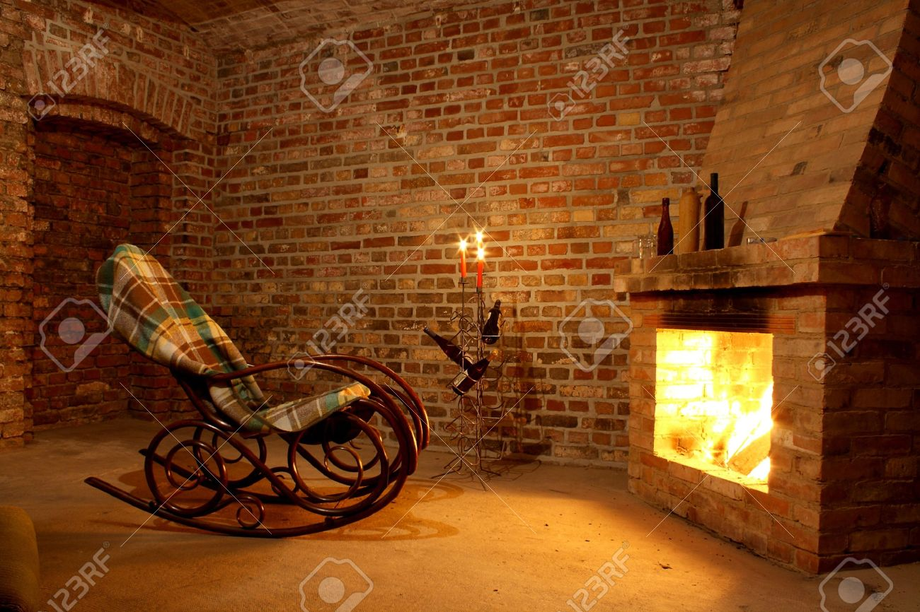 Rocking Chair By The Fireplace In Brick Room With Candles Stock ...