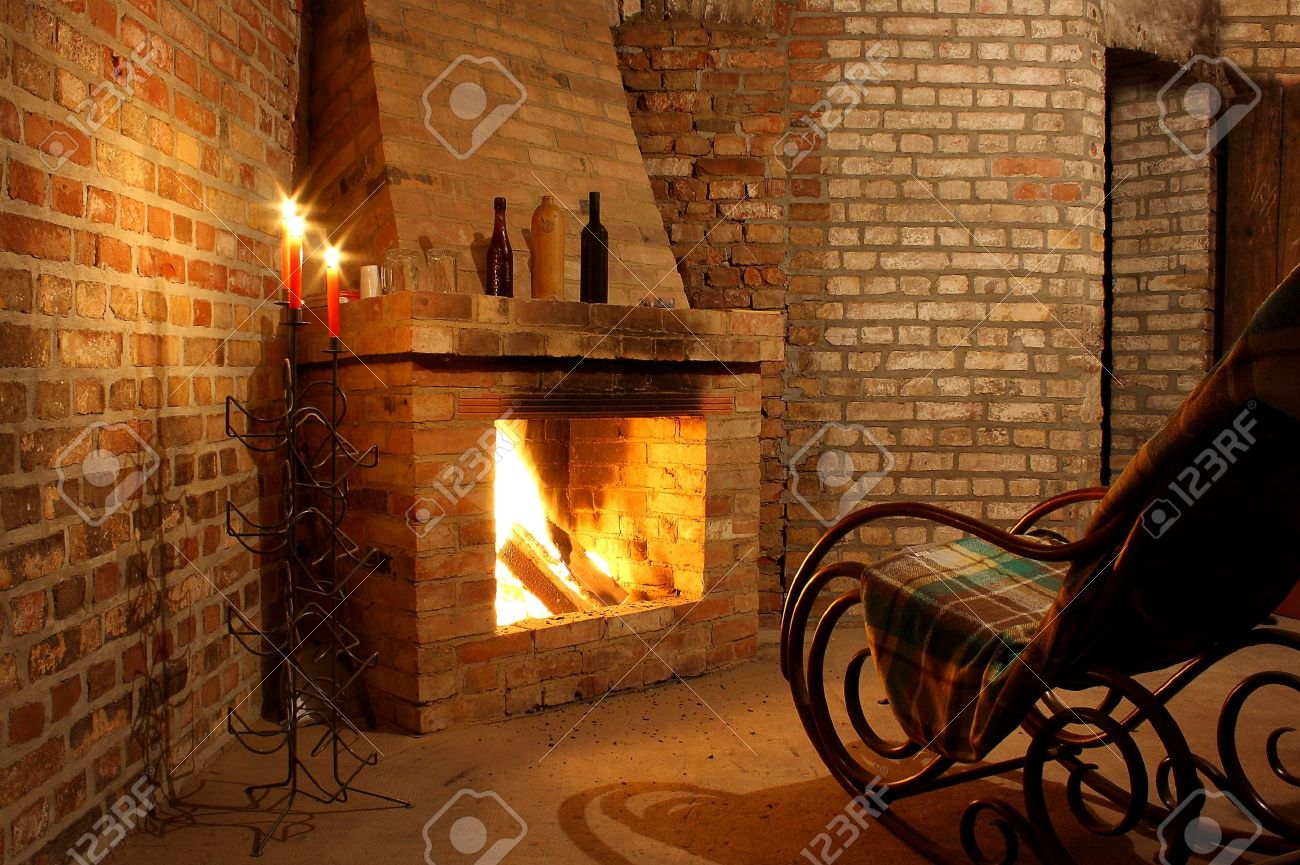 Etonnant Rocking Chair By The Fireplace In Brick Room And Candles Stock Photo    17361736