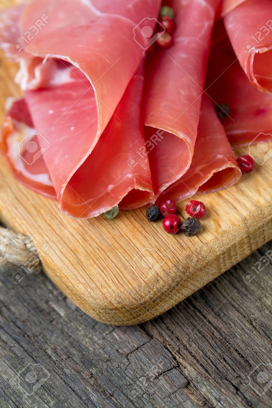 sliced prosciutto on a wooden table Stock Photo - 22956807