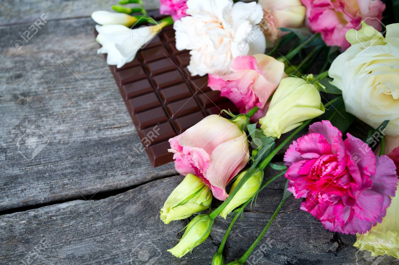 Bouquet Of Beautiful Flowers And Chocolate On Wooden Surface Stock