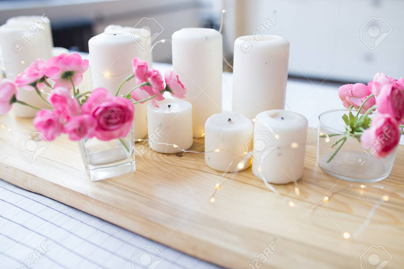 Candles with lights composition on the table cute home decor with candles and flowers