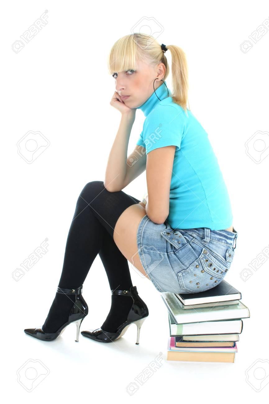 sad schoolgirl in blue sitting on stacked books Stock Photo - 7631793
