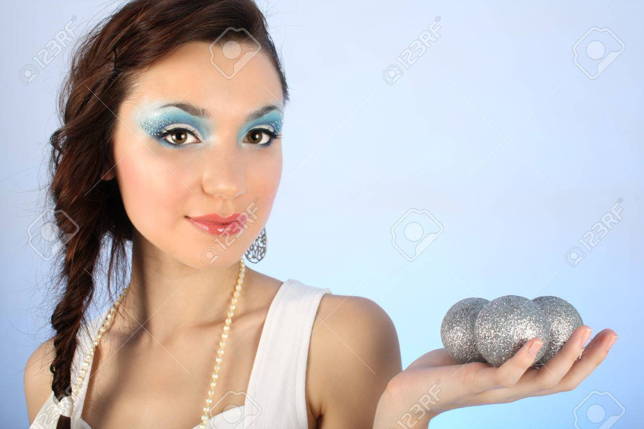 portrait of beautiful woman with christmas tree balls over blue background Stock Photo - 8275691